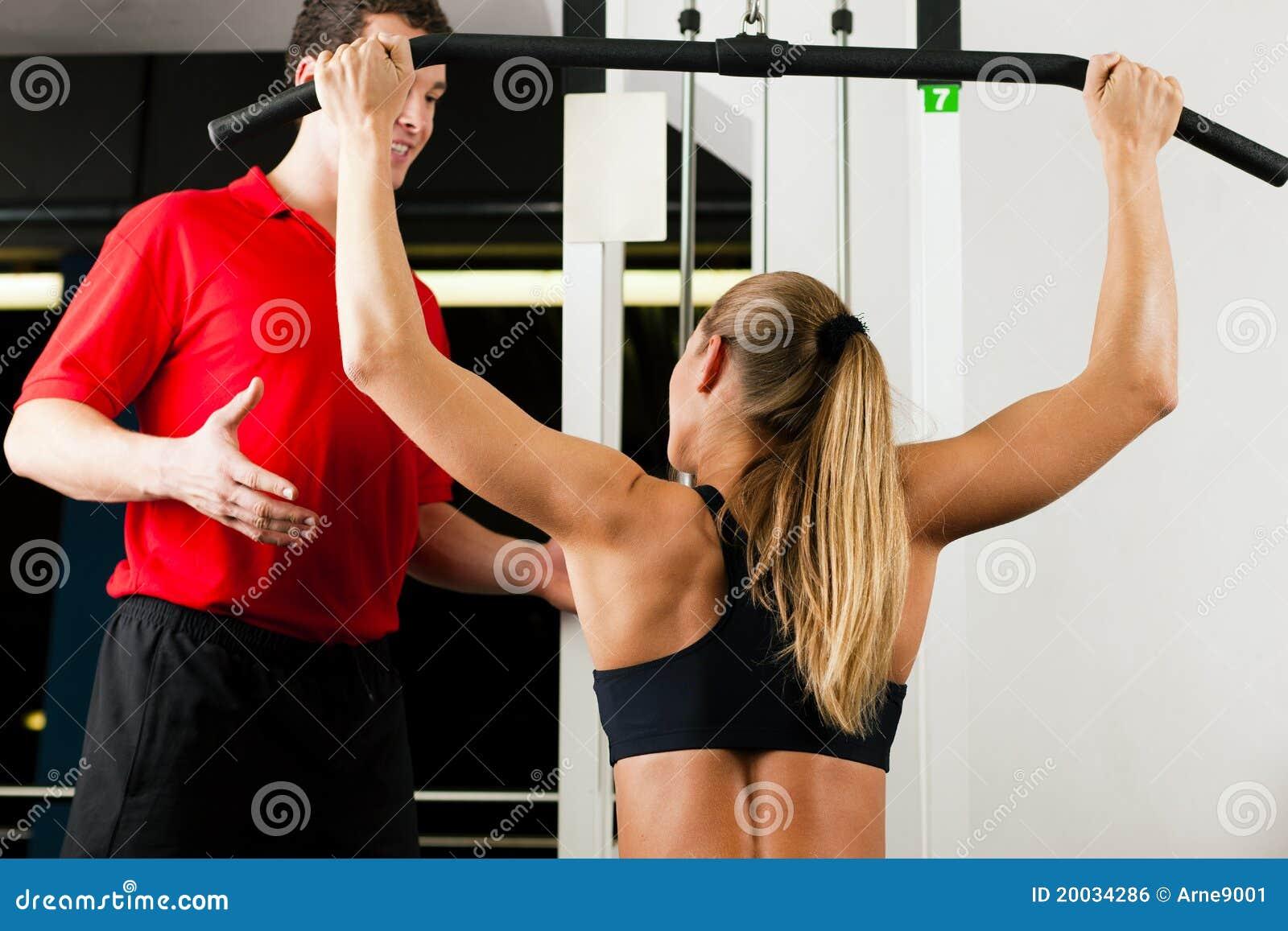 Mujer con el amaestrador personal en gimnasia