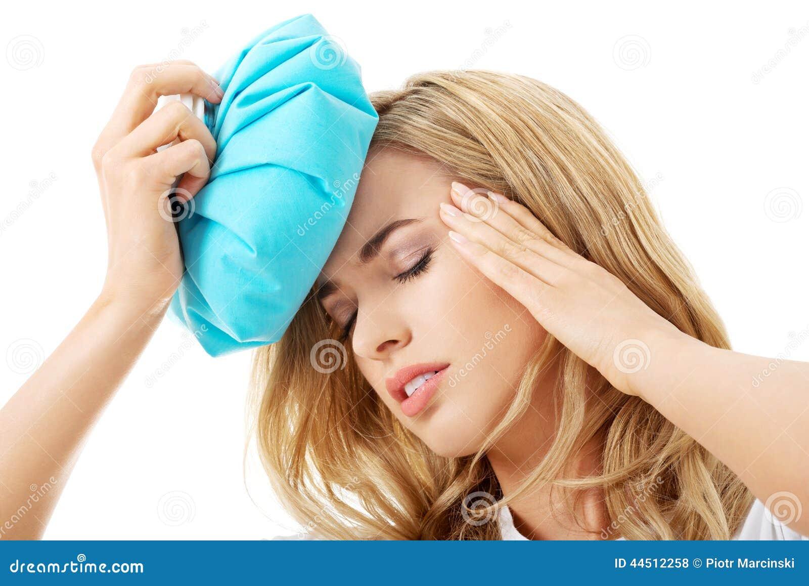 Mujer con el bolso de hielo, teniendo dolor de cabeza