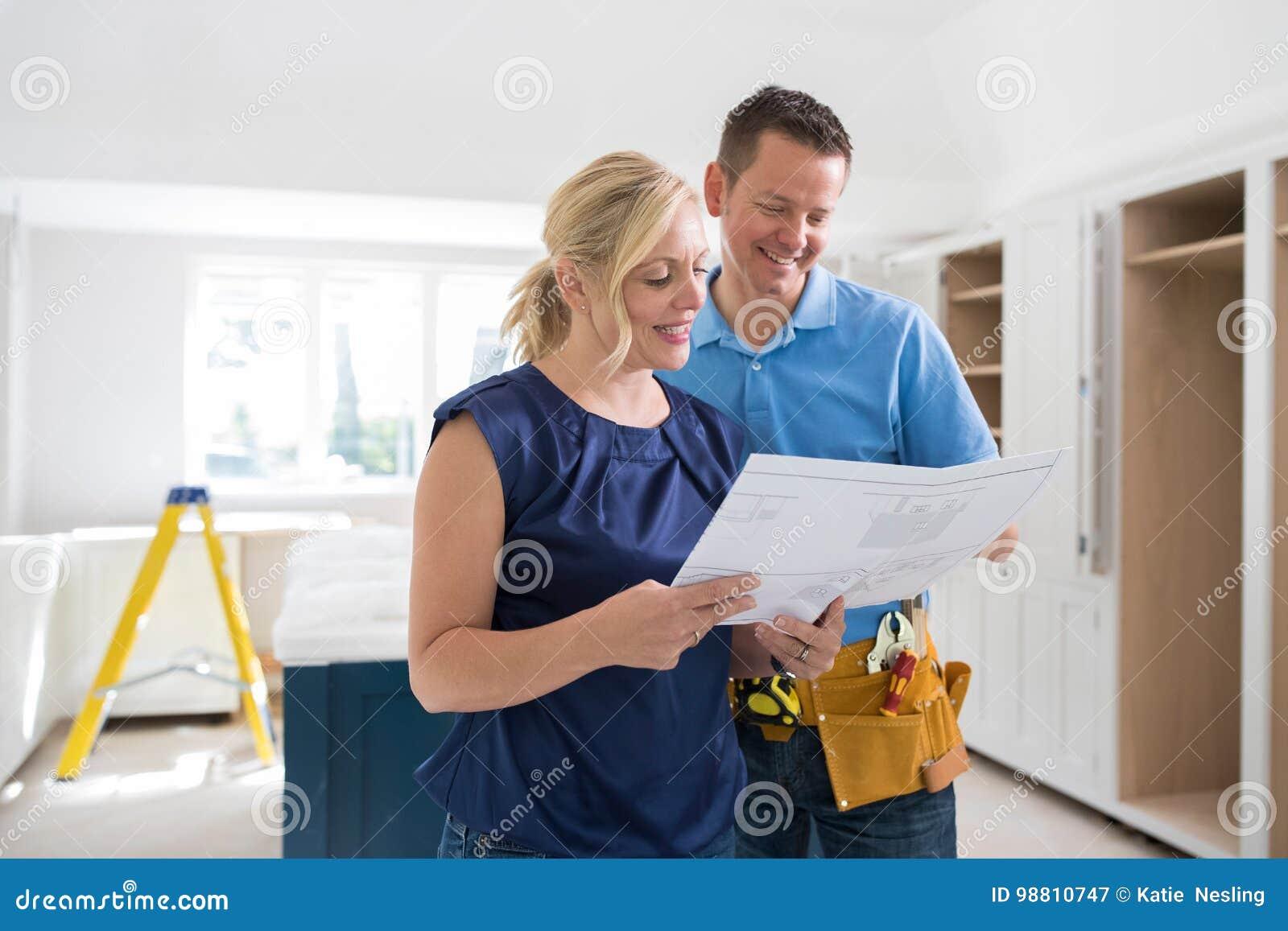 Mujer con el carpintero Looking At Plans para la nueva cocina