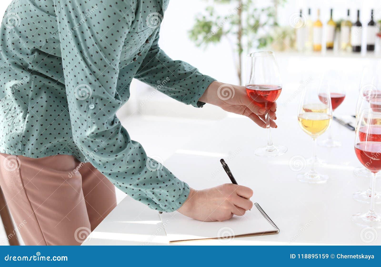 Mujer con el cuaderno que prueba el vino delicioso
