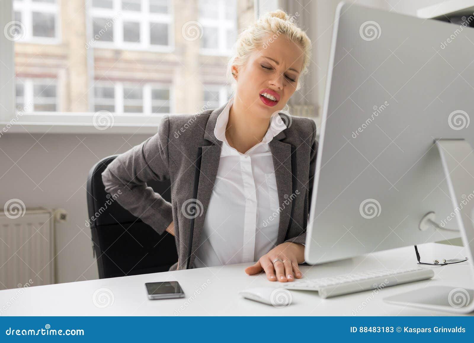 Mujer con el dolor de espalda que se sienta por el ordenador en la oficina