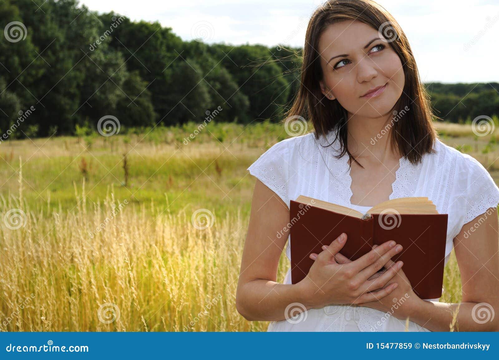 Mujer con el libro en campo