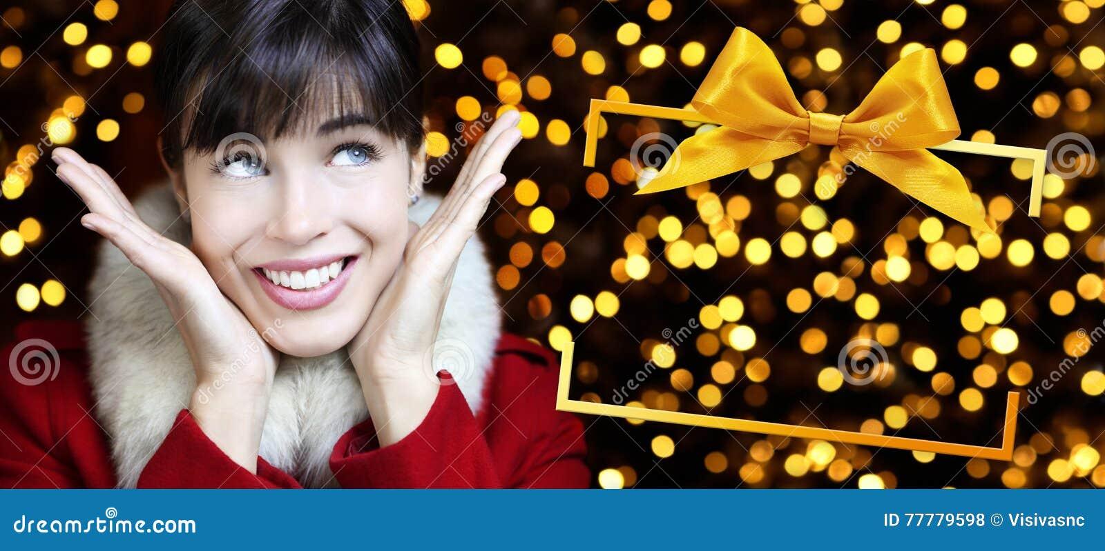 Mujer con el marco de caja de la Navidad en luces de oro