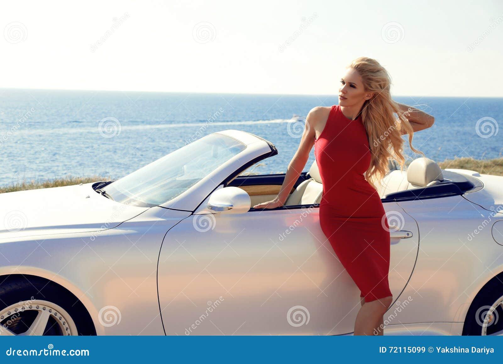 d25f6bbc31df Mujer Con El Pelo Rubio En El Vestido Rojo Que Presenta Al Lado Del ...