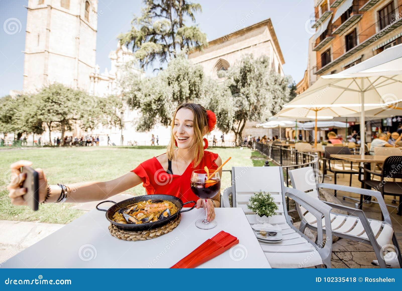 Mujer con el plato de la paella en Valencia