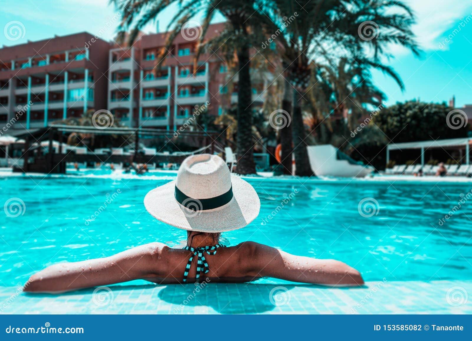 Mujer con el sunhat que se relaja en piscina en el balneario
