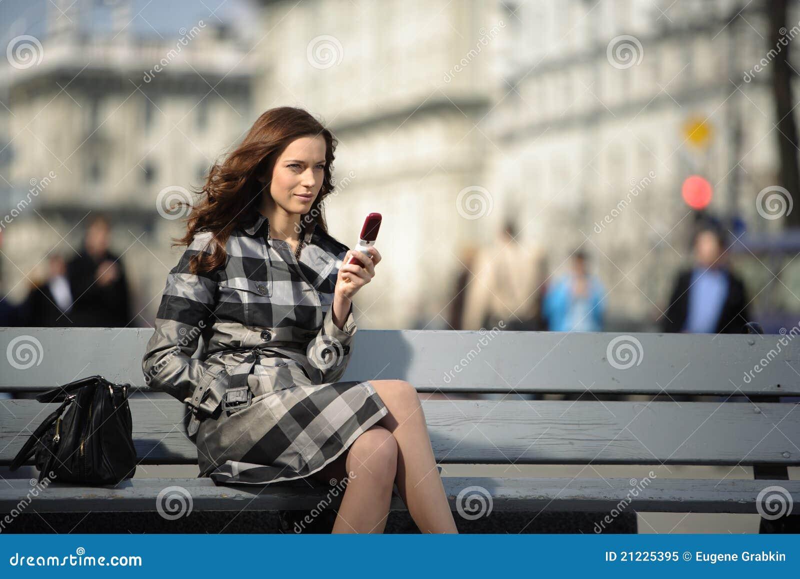 Mujer con el teléfono móvil en el fondo de la ciudad