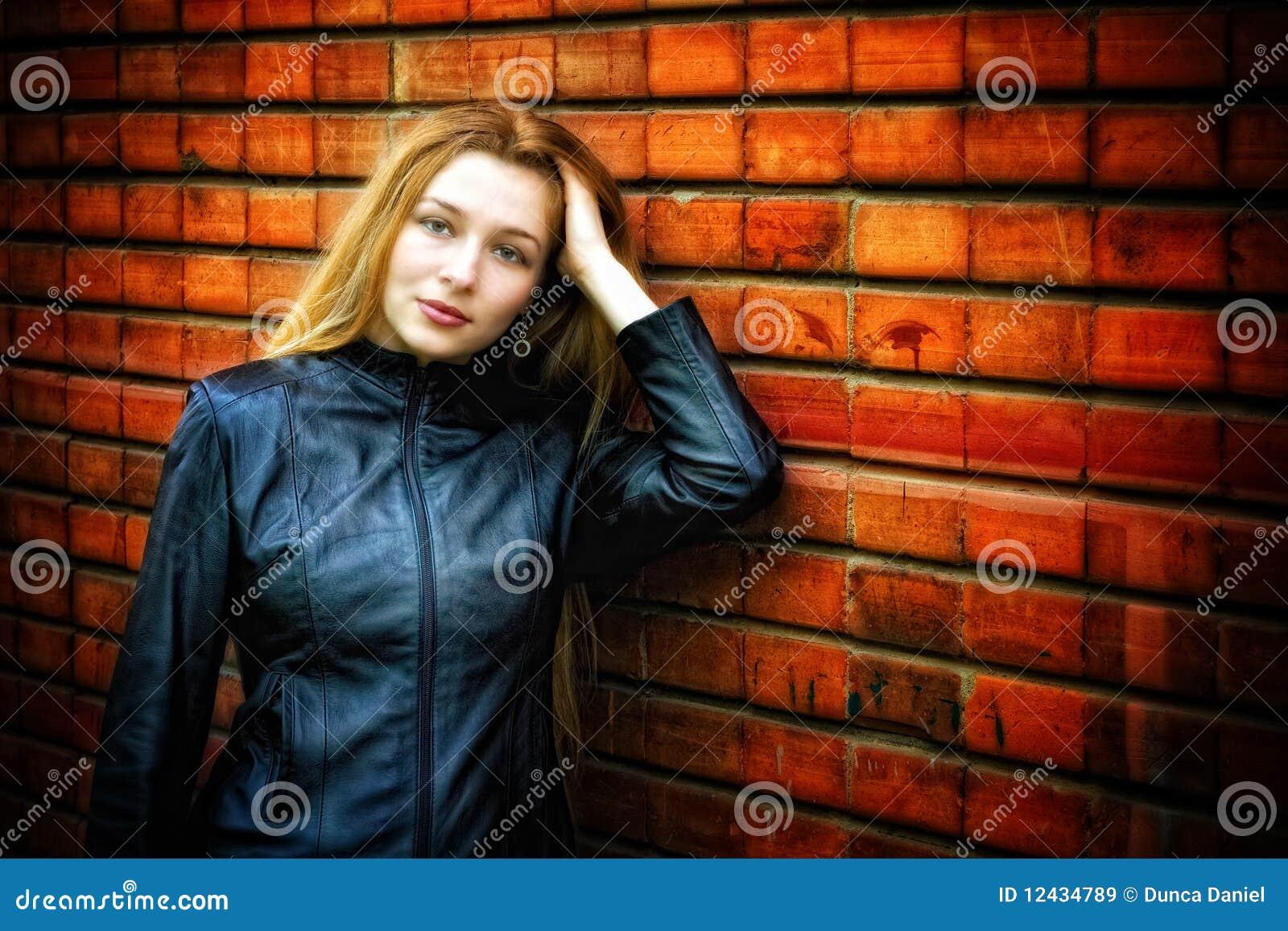 Mujer con estilo atractiva en la pared cercana de cuero