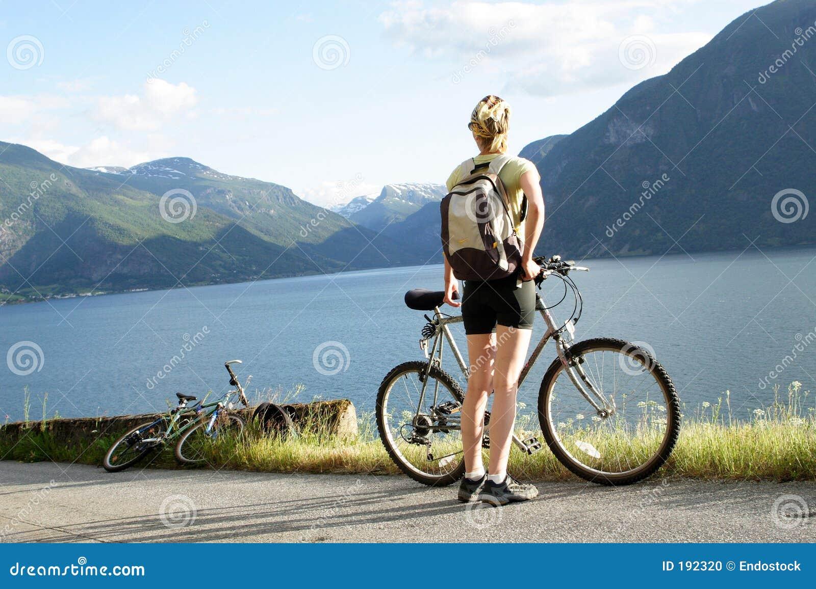 Mujer con la bici sobre el fiordo