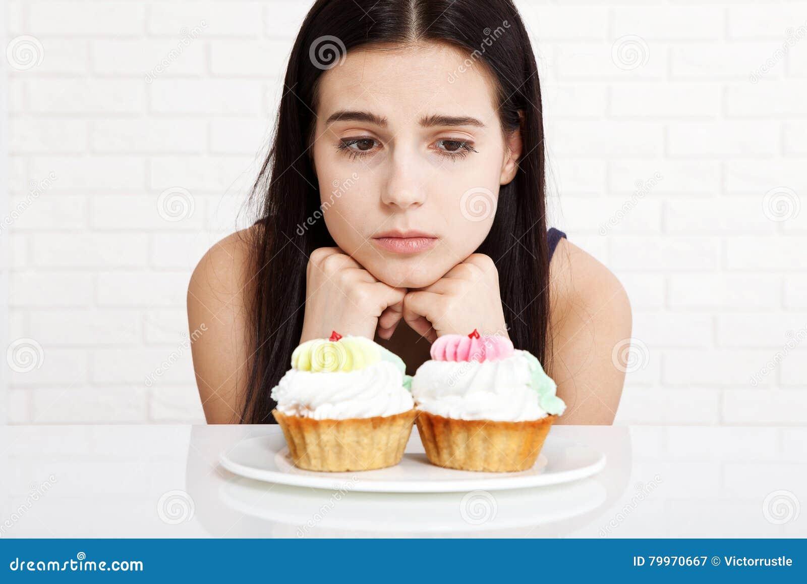Mujer con la cara del primer de la torta Las mujeres hermosas miran tristemente la torta Mujer asiática Foco selectivo