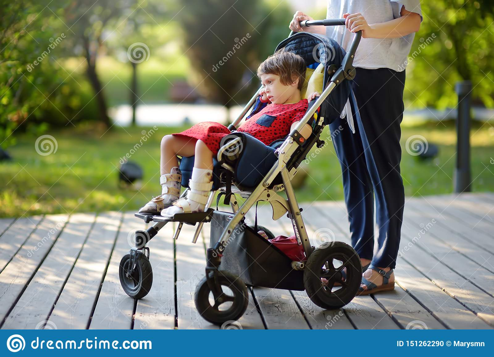 Mujer con la muchacha discapacitada en una silla de ruedas que camina en el verano del parque Parálisis cerebral del niño Familia