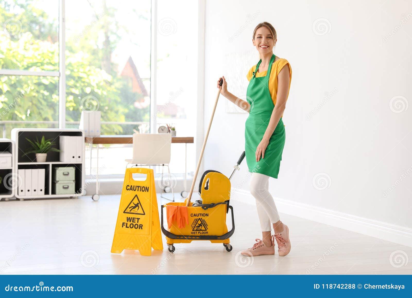 Mujer con la oficina de la limpieza de la fregona y del cubo