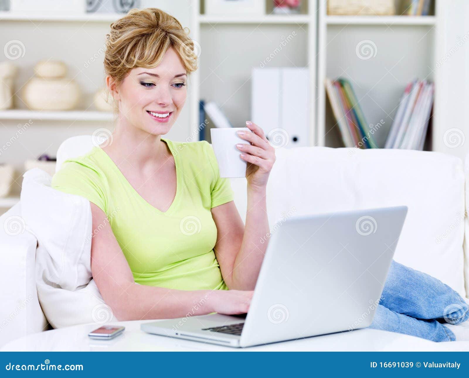 Mujer con la taza de café y de computadora portátil en el país