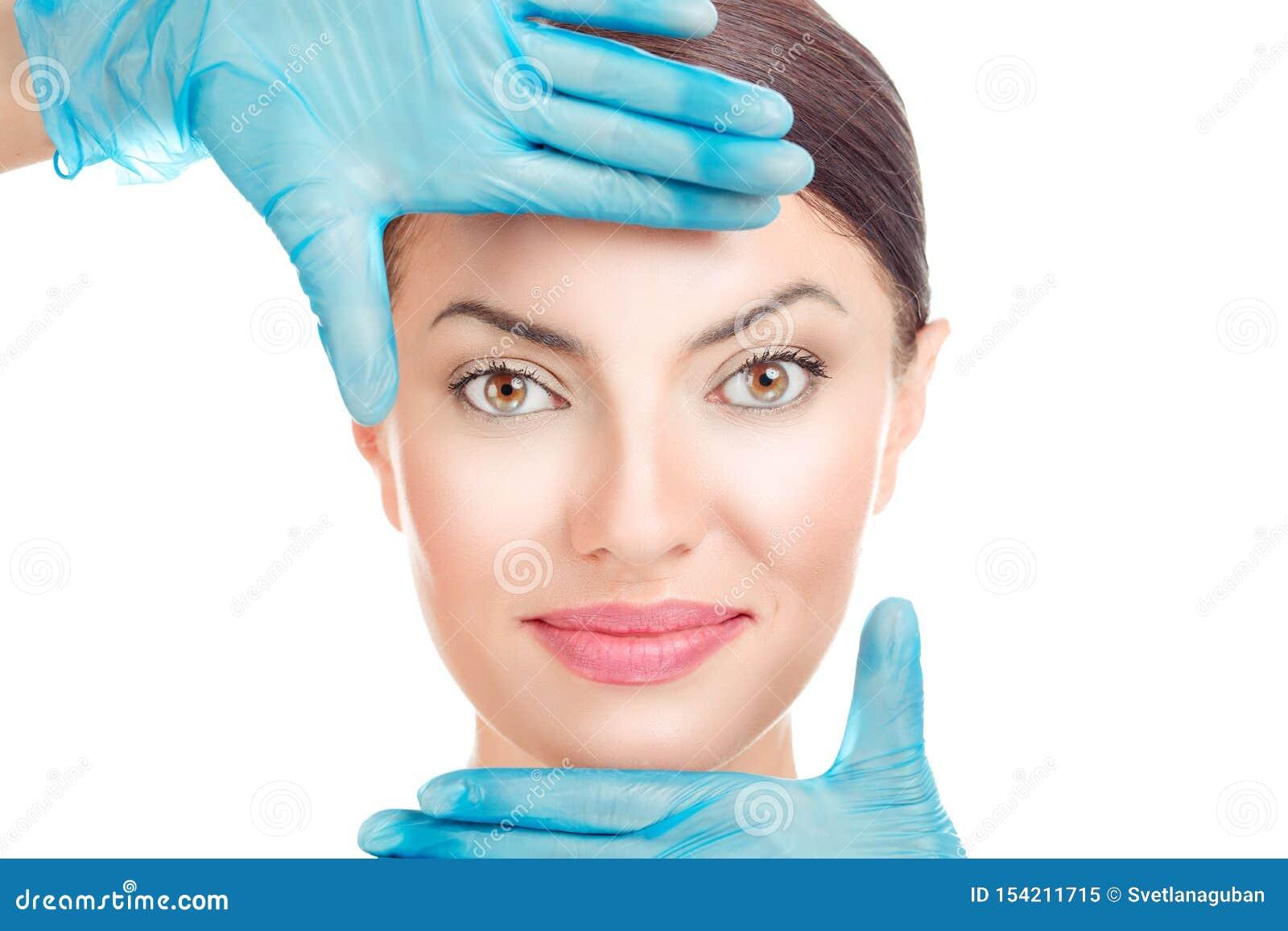 Mujer con las manos de los doctores en guantes alrededor de la cara
