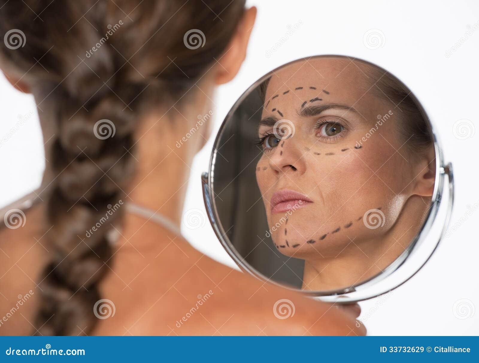 Mujer con las marcas de la cirugía plástica en la cara que mira en espejo