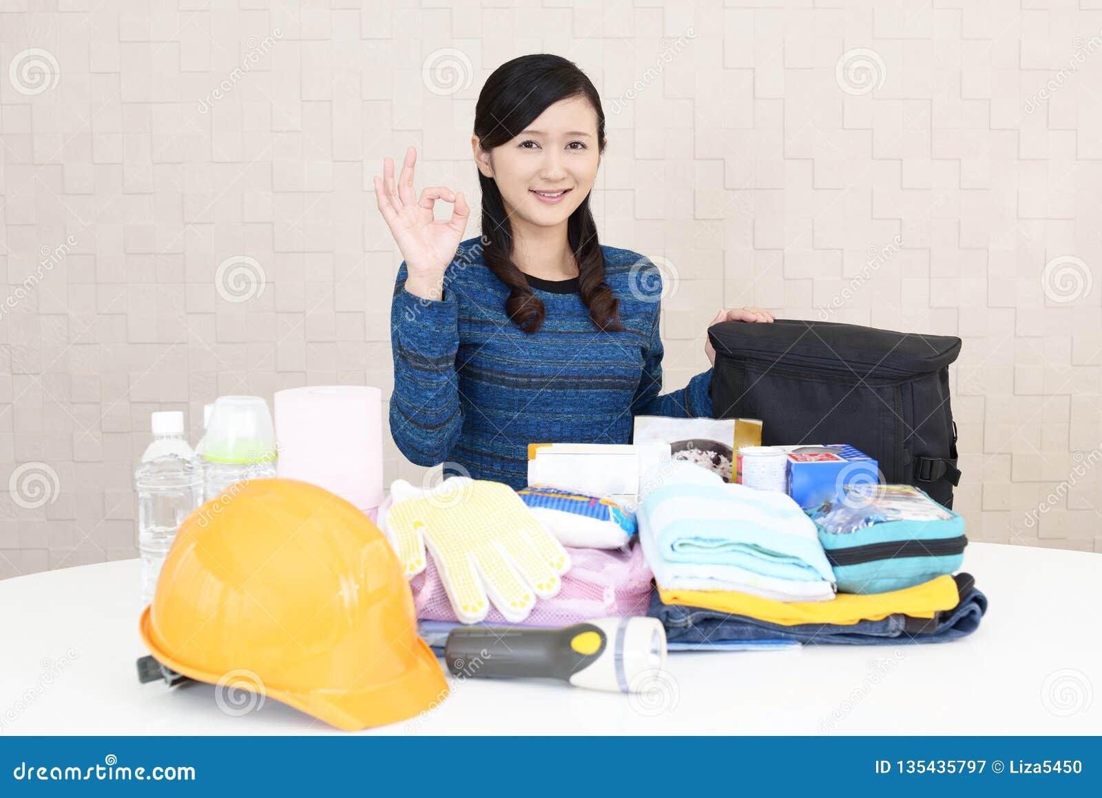 Mujer con las mercancías de la prevención de desastre