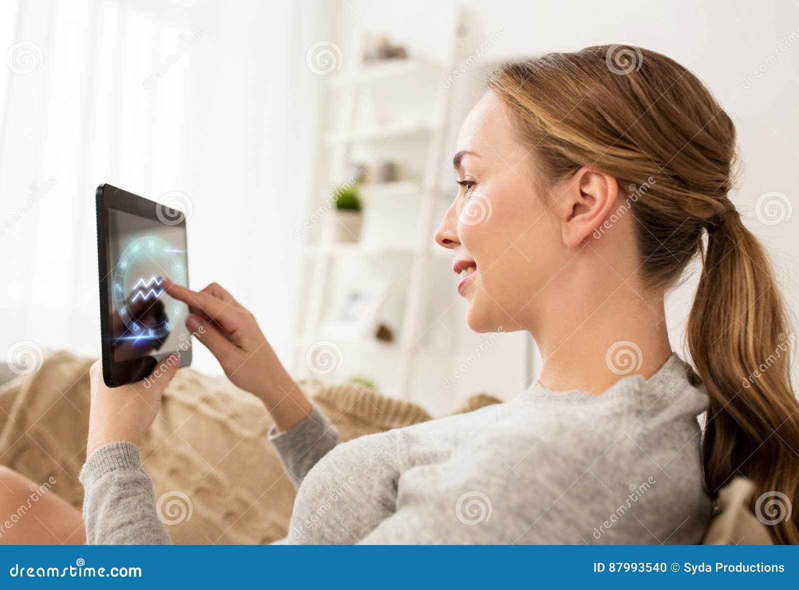 Mujer con las muestras de la PC y del zodiaco de la tableta en casa