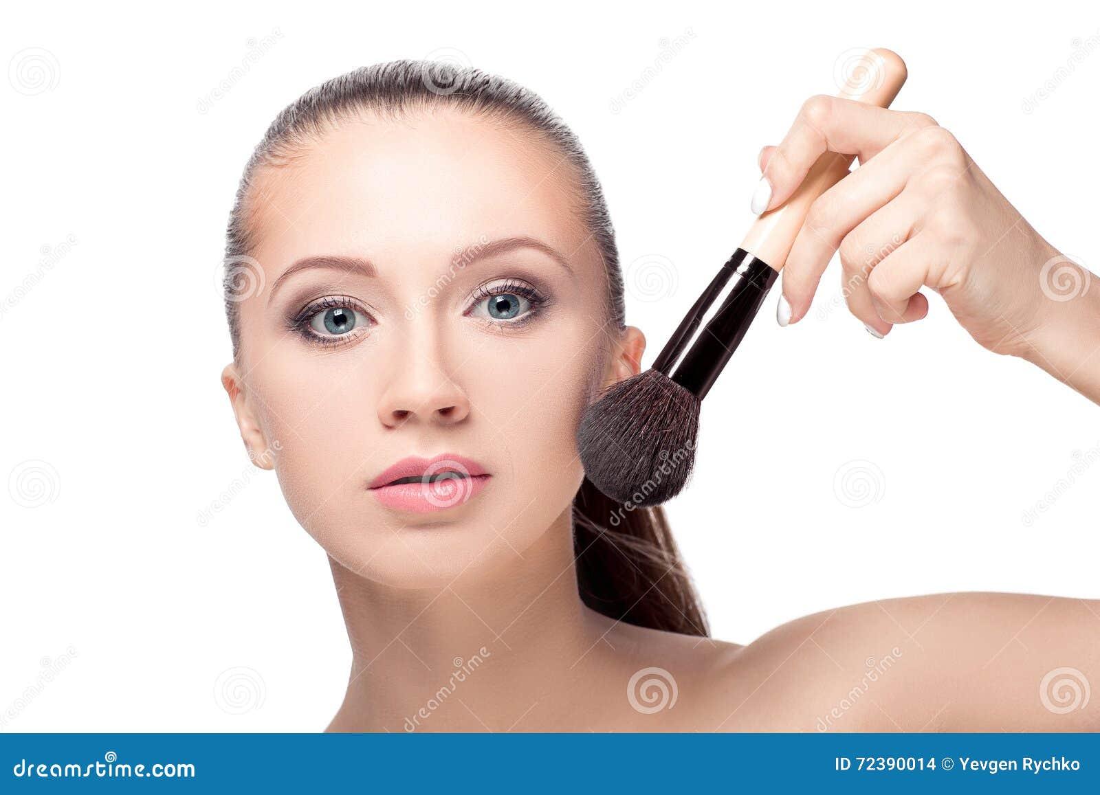 Mujer con los cepillos del maquillaje