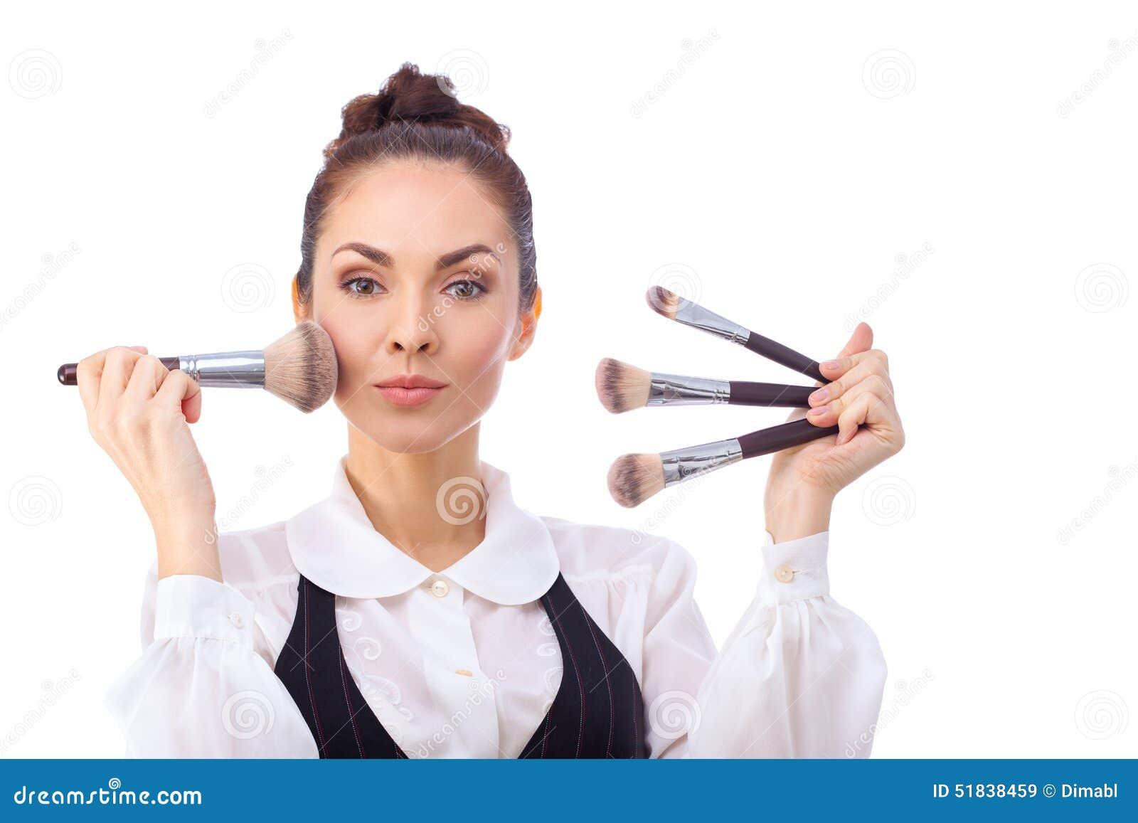 Mujer con los cepillos del maquillaje Todos aislados en blanco