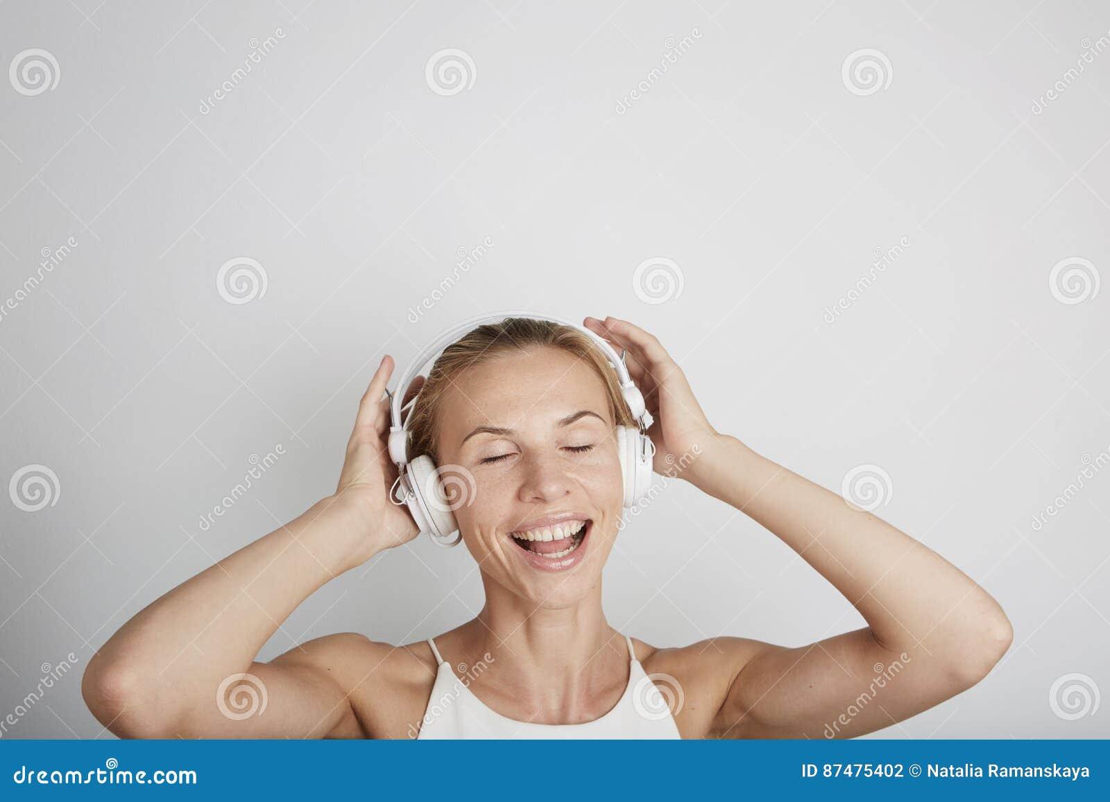 Mujer con música que escucha de los auriculares