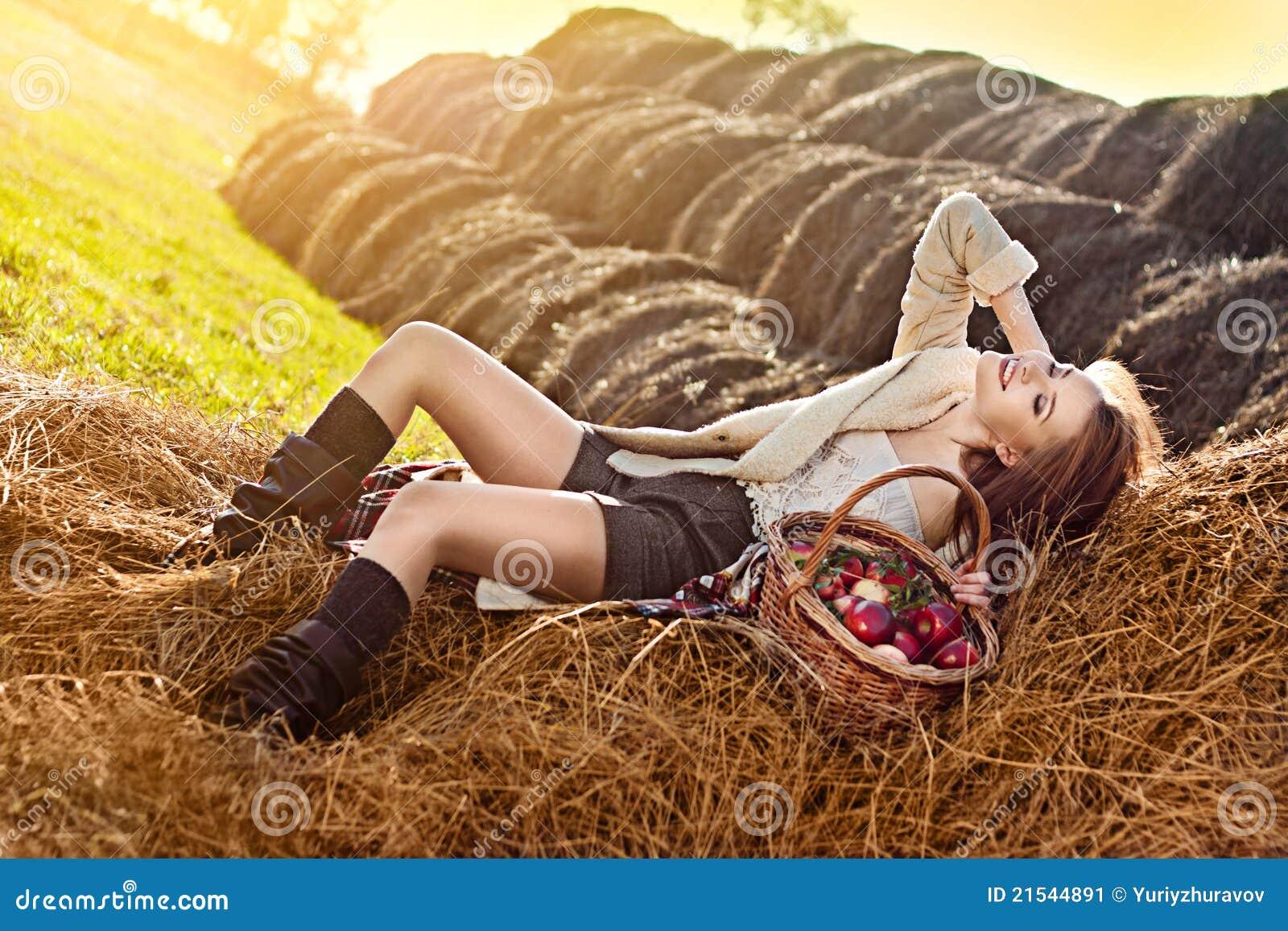 Mujer con muchos manzana en cesta en haystack