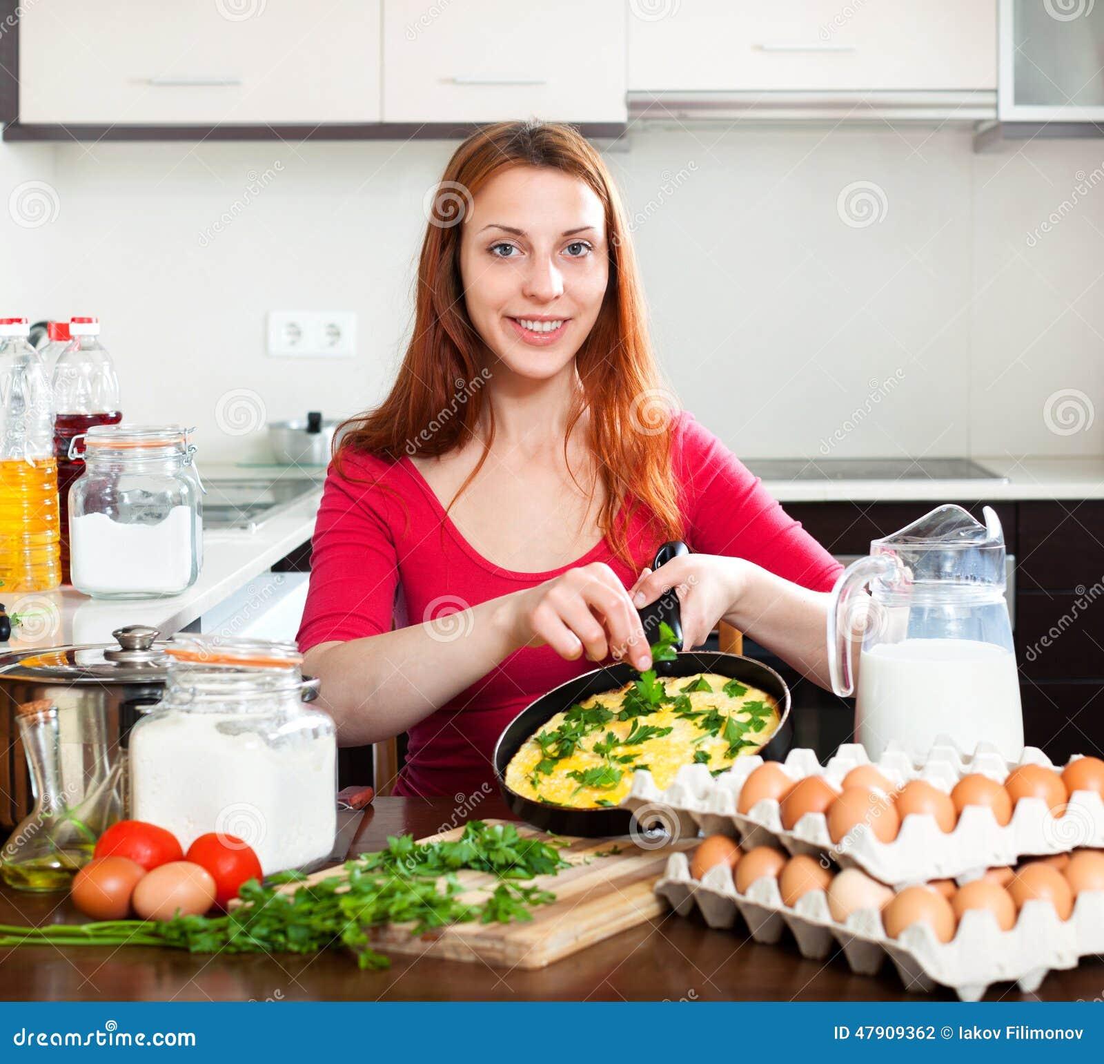 Mujer con omlet cocinado en cocina de la cacerola en casa - La cocina en casa ...