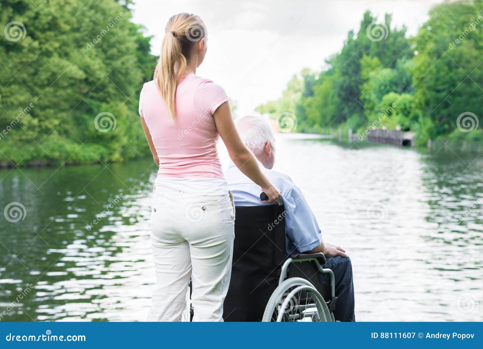 Mujer con su padre discapacitado On Wheelchair Looking en el lago