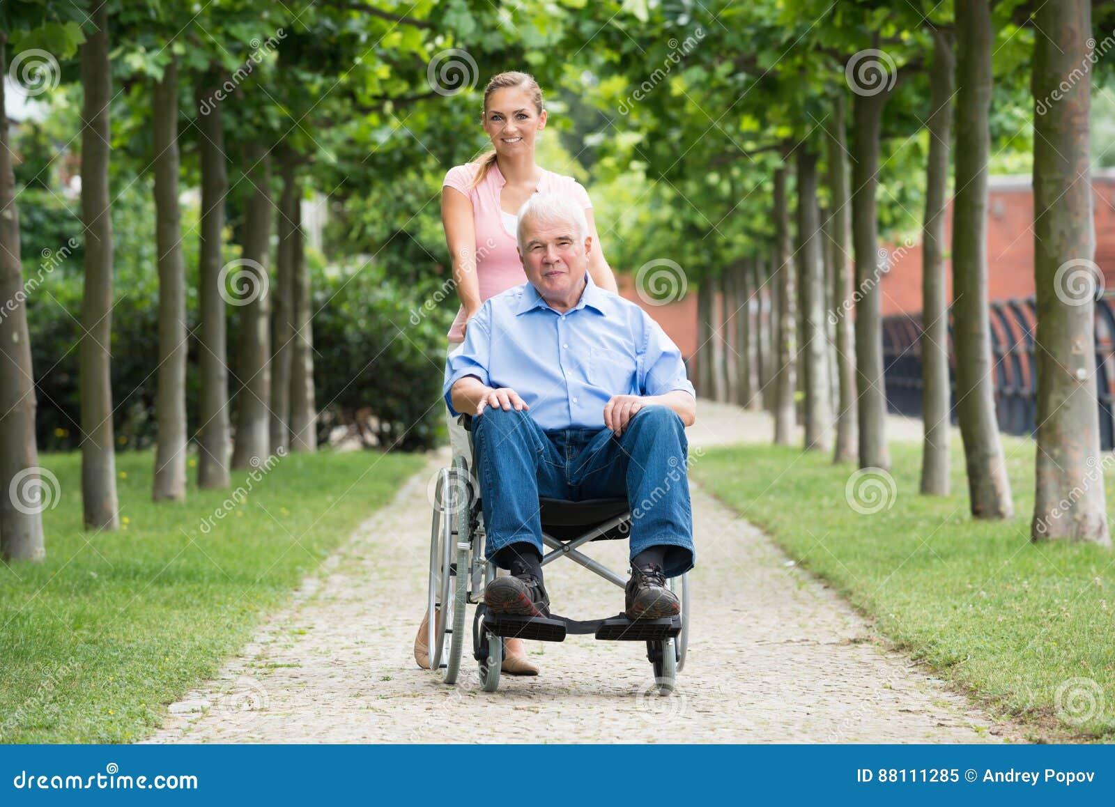 Mujer con su viejo padre mayor On Wheelchair