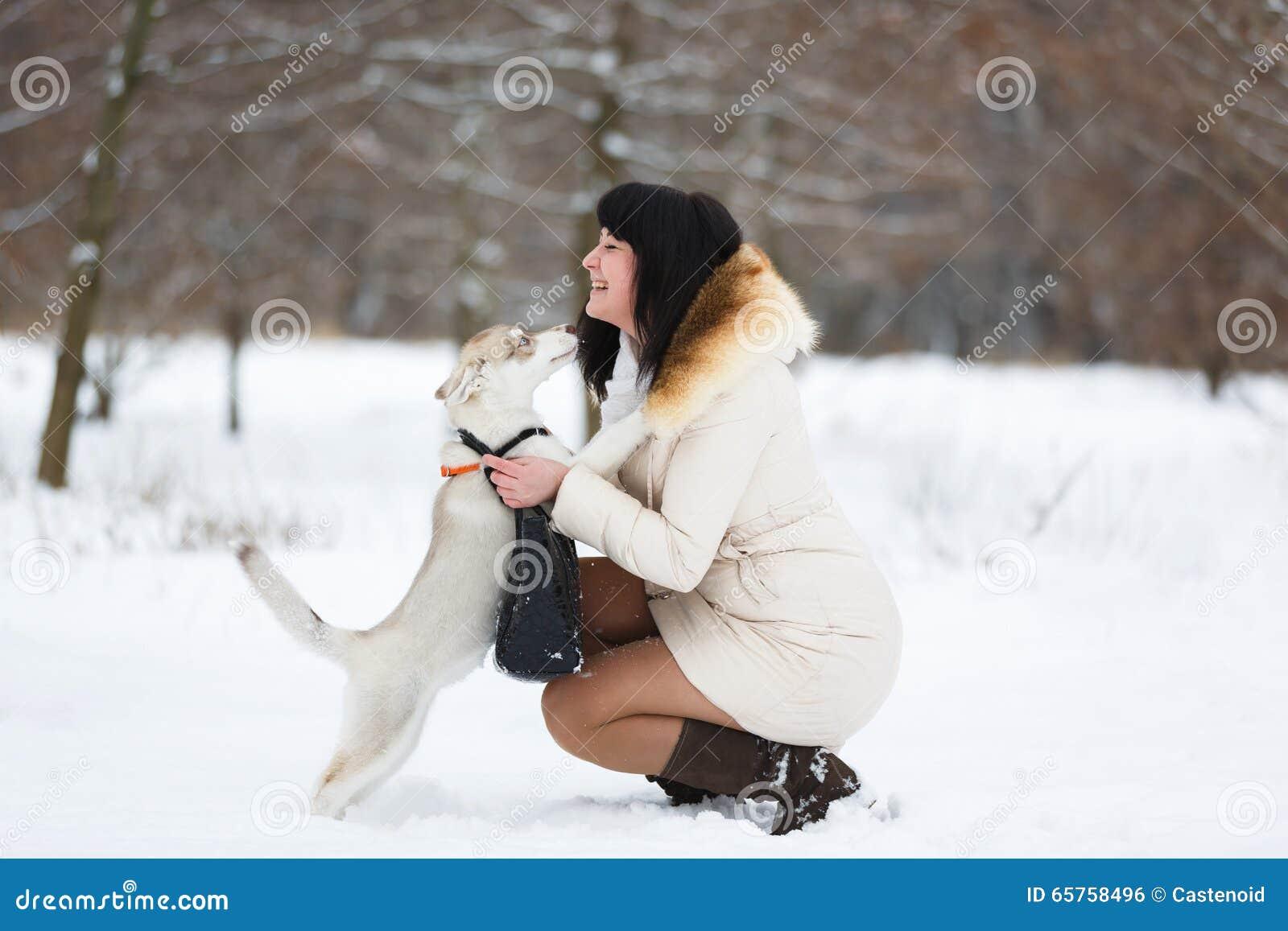 Mujer con un perrito fornido apacible