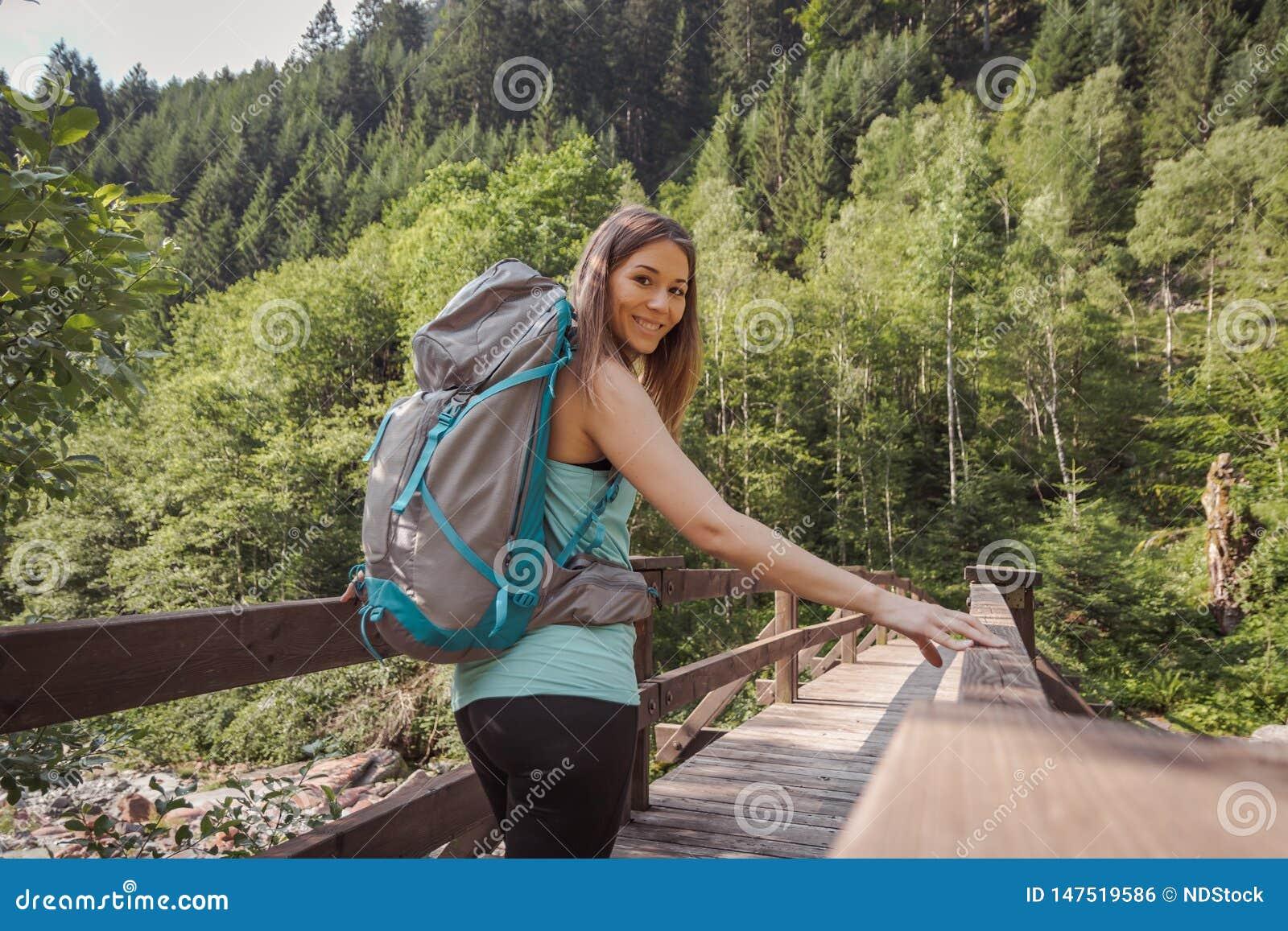 Mujer con una mochila que camina en un puente en el bosque