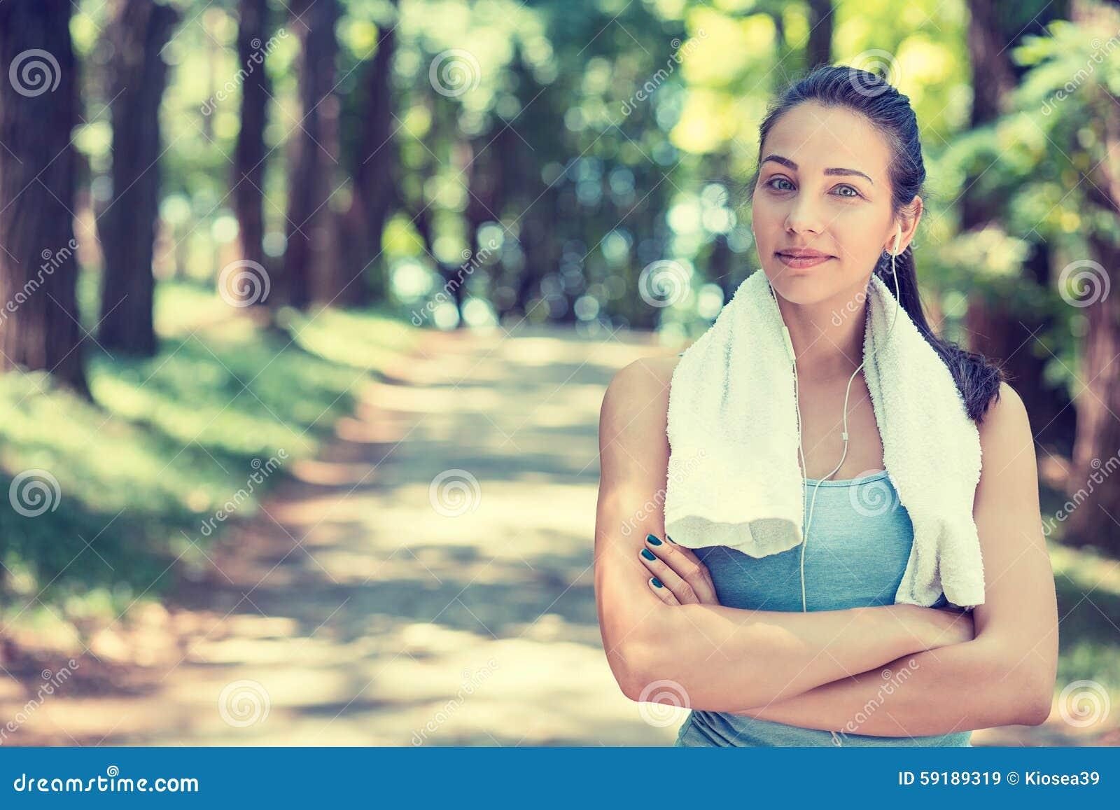 Mujer confiada del ajuste con la toalla blanca que descansa después de entrenamiento
