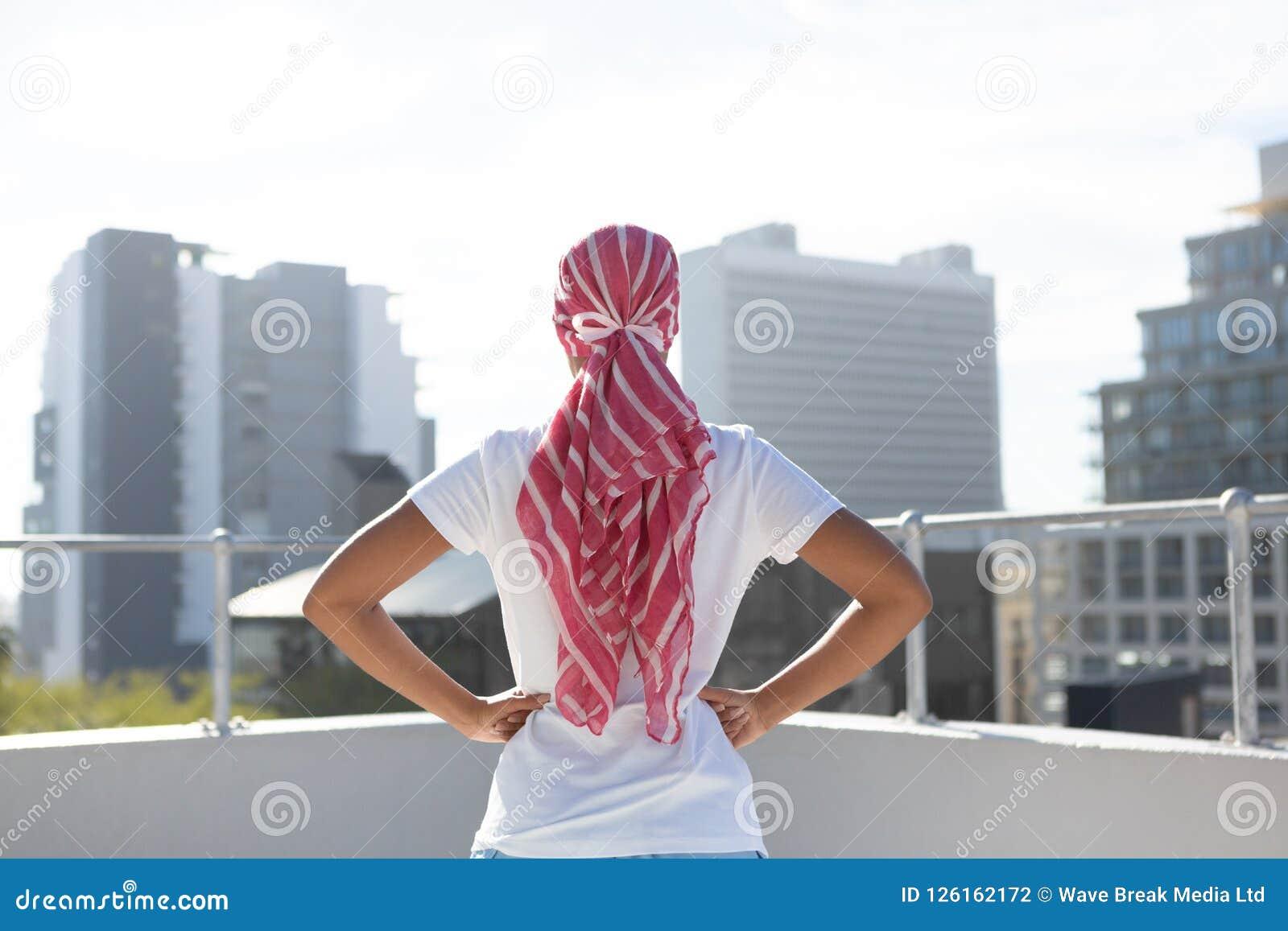 Mujer confiada que se coloca en la ciudad para la conciencia del cáncer de pecho