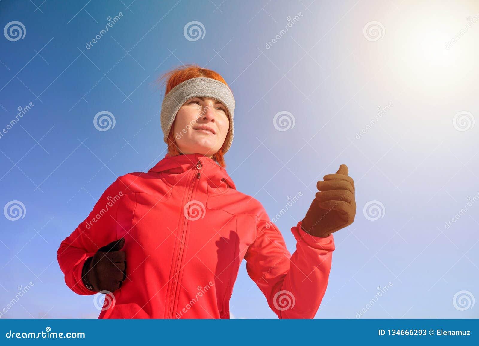 Mujer corriente del deporte Corredor femenino que activa en el parque frío del invierno que lleva la ropa y guantes corrientes de