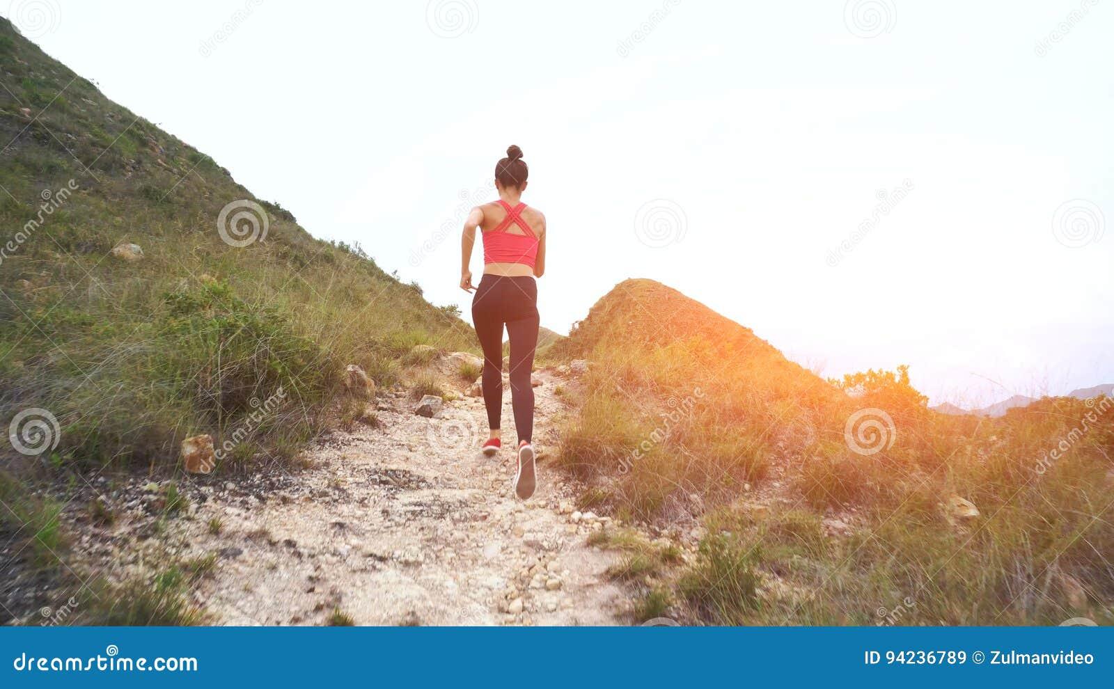 3285b3b36dd Mujer corriente en el camino de la montaña Muchacha del deporte que  ejercita afuera en montañas