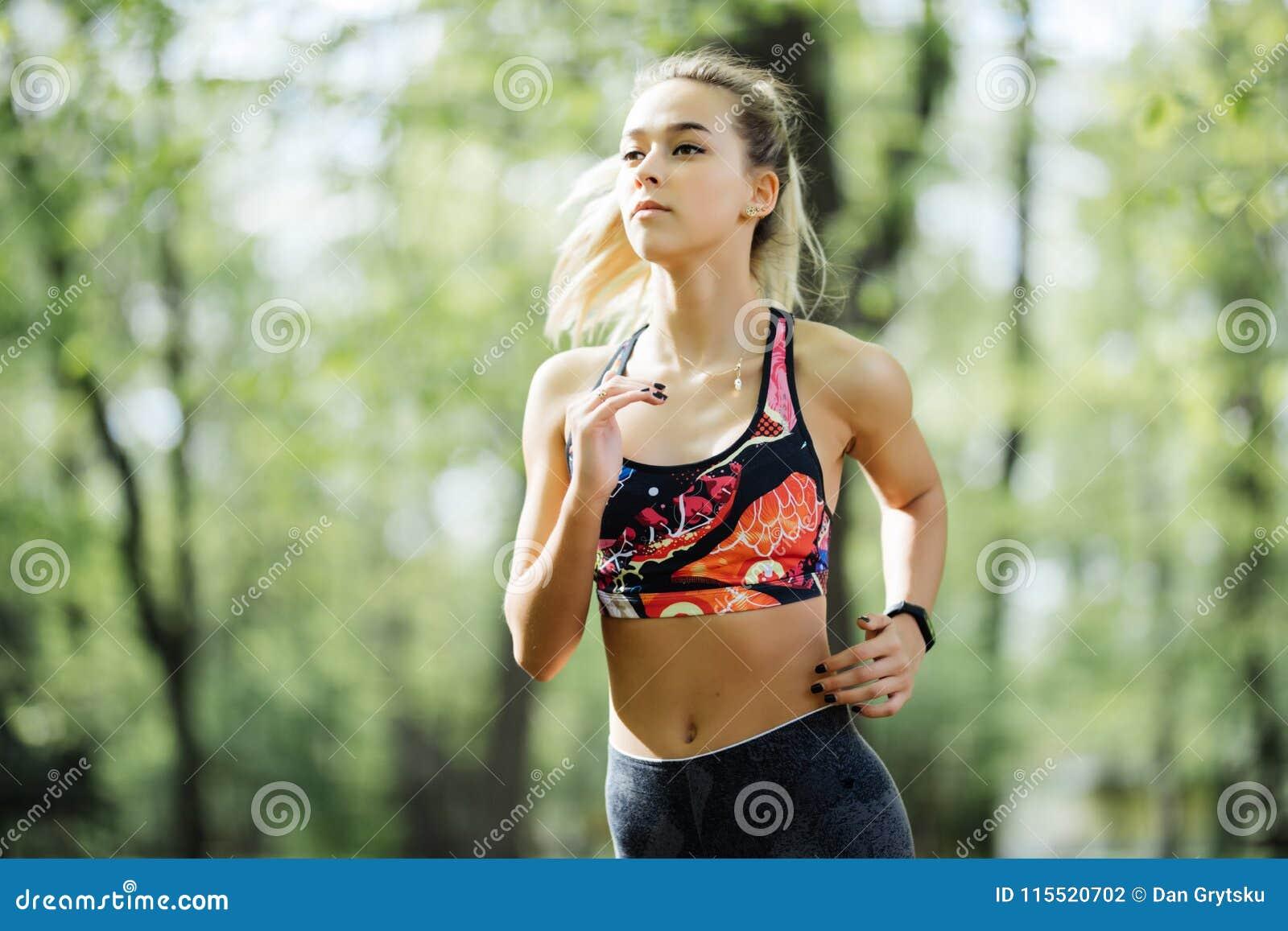 Mujer corriente en parque en el entrenamiento del verano Modelo joven de la aptitud del deporte en ropa corriente deportiva