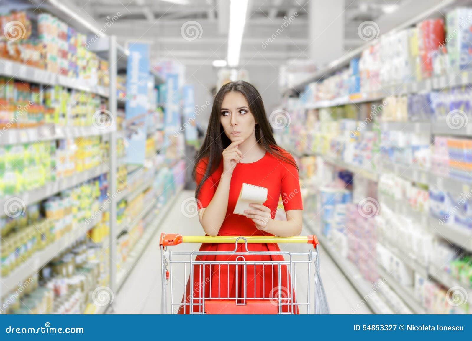 Mujer curiosa en el supermercado con la lista de compras