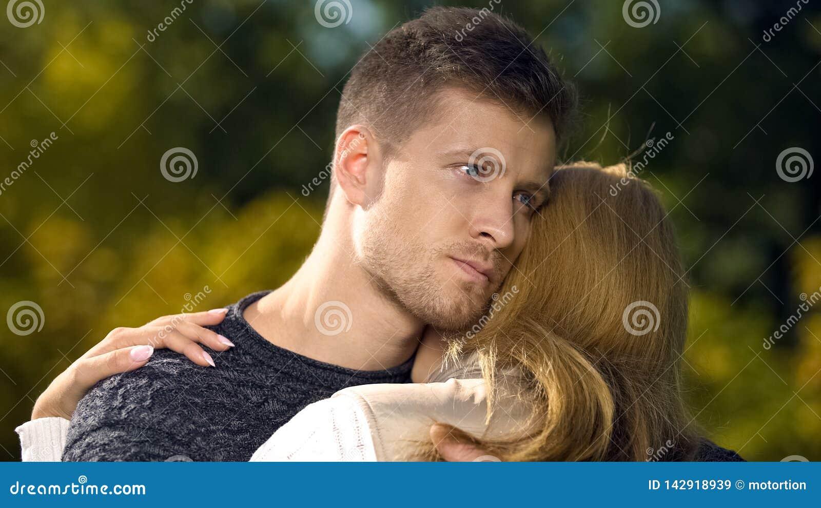 Mujer de abarcamiento del hombre preocupante, apoyando después de pérdida de persona cercana, cuidado