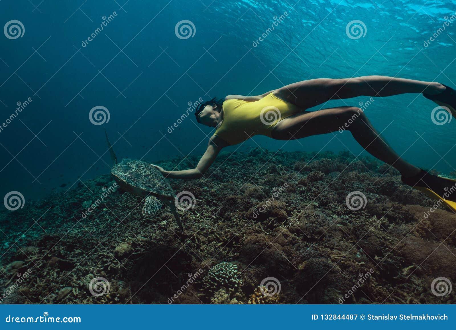 Mujer de Freediver con la tortuga, fotografía subacuática