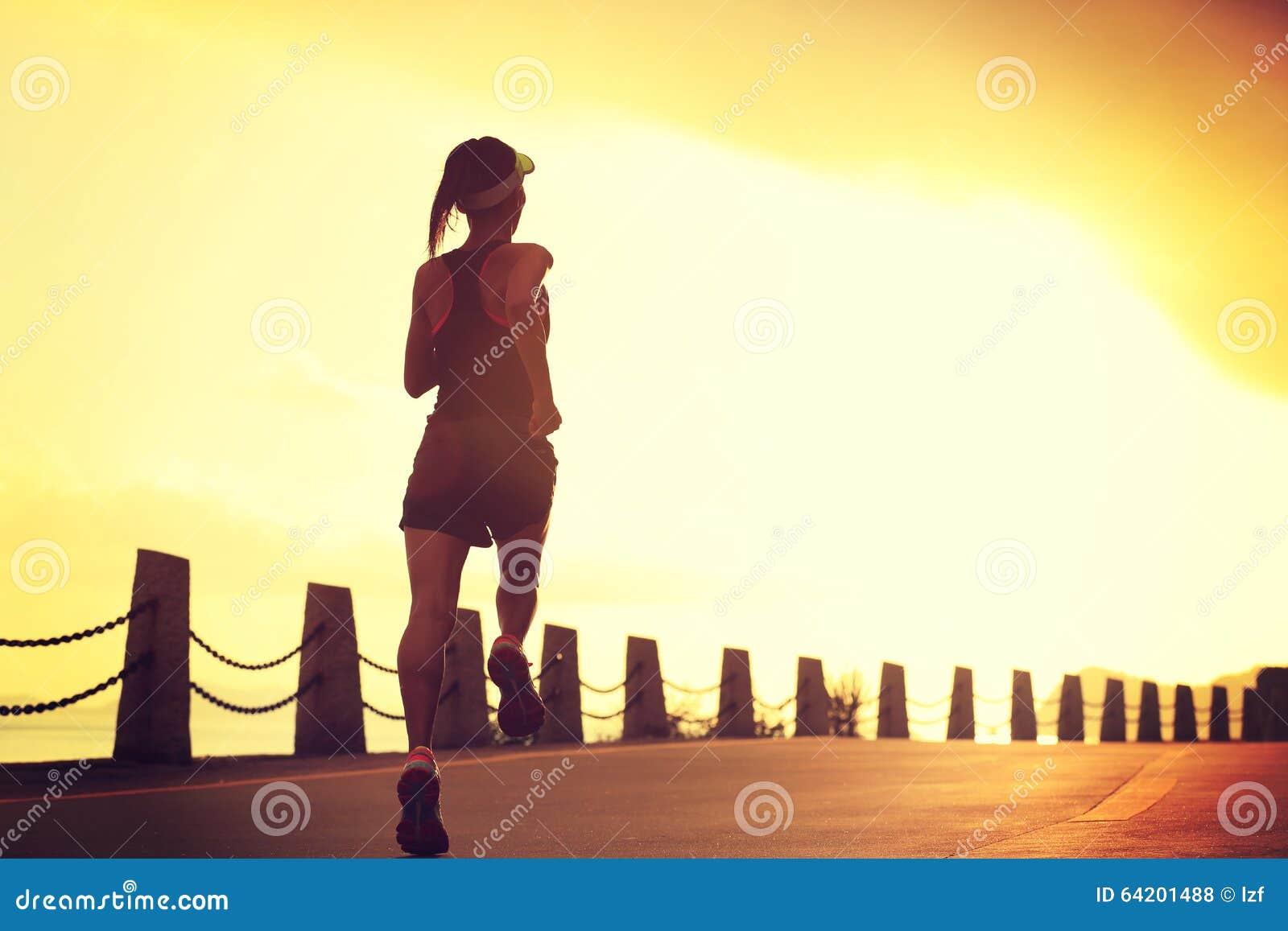 Mujer de la aptitud que corre en rastro de la playa de la salida del sol