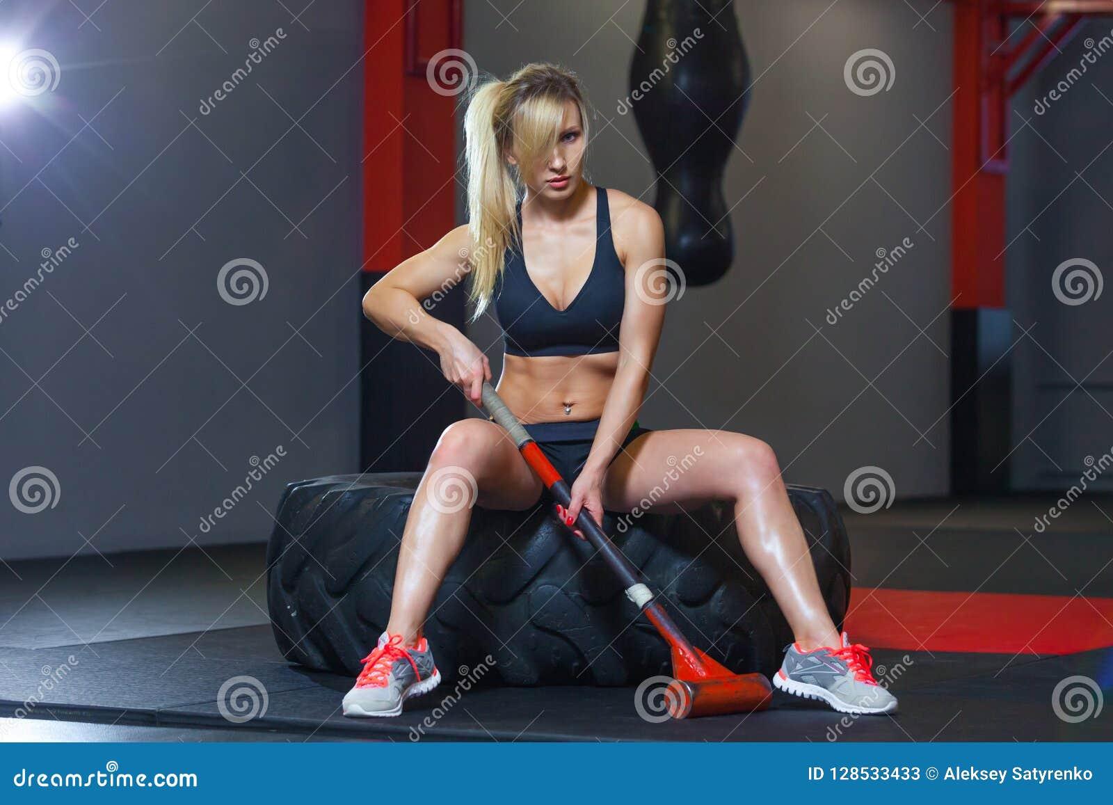 Mujer de la aptitud que golpea el neumático de la rueda con el trineo del martillo en el gimnasio