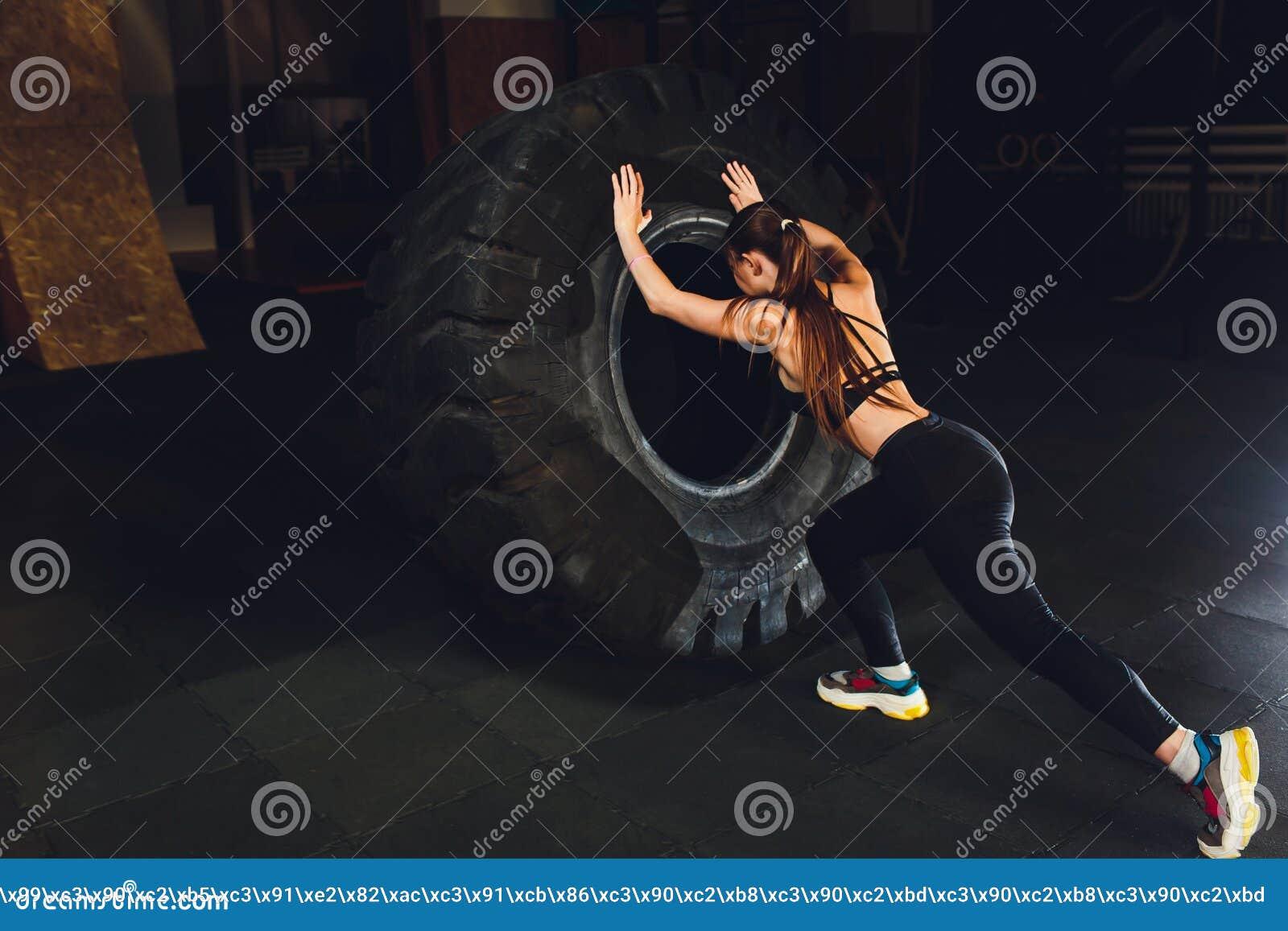 Mujer de la aptitud que mueve de un tir?n el neum?tico de la rueda en gimnasio Atleta de sexo femenino apto que se resuelve con u