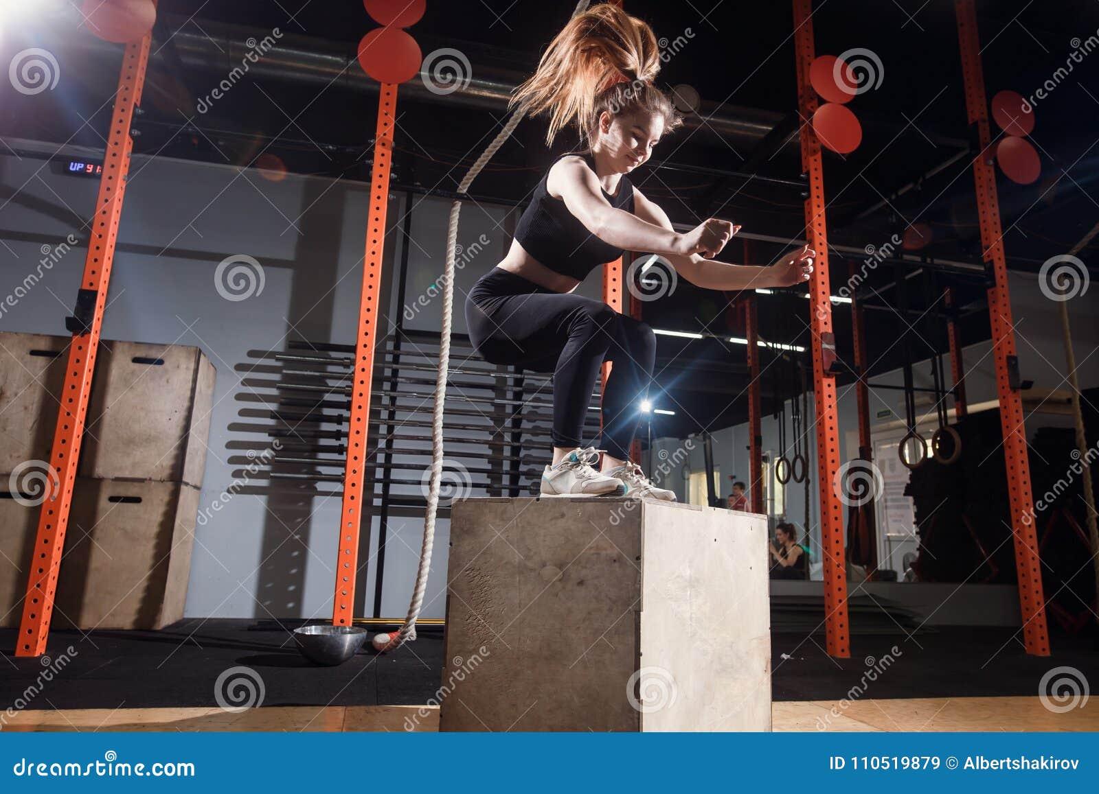 Mujer de la aptitud que salta en el entrenamiento en el gimnasio, ejercicio apto de la caja de la cruz