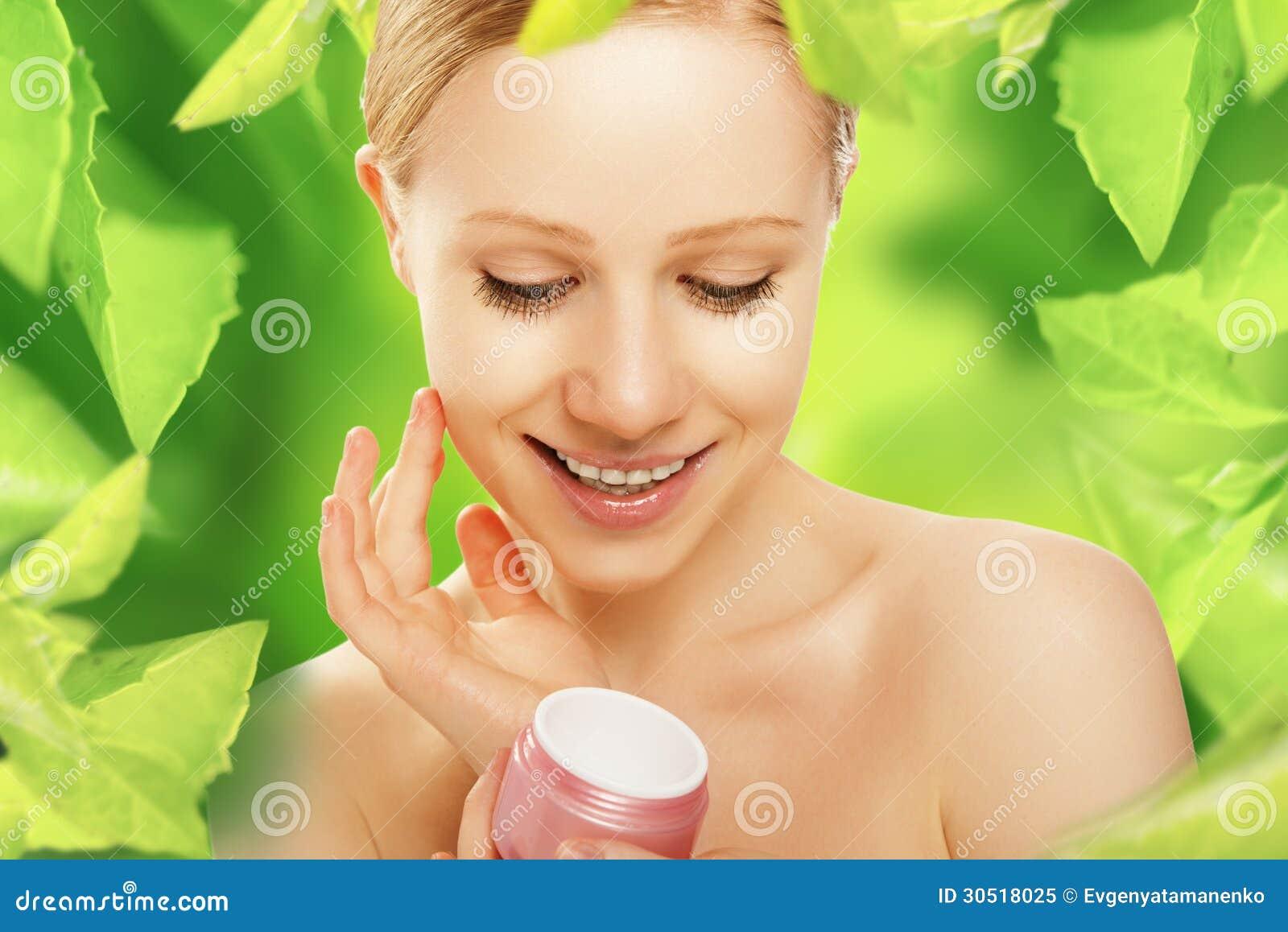 Mujer de la belleza con el cuidado de piel poner crema y natural en verde
