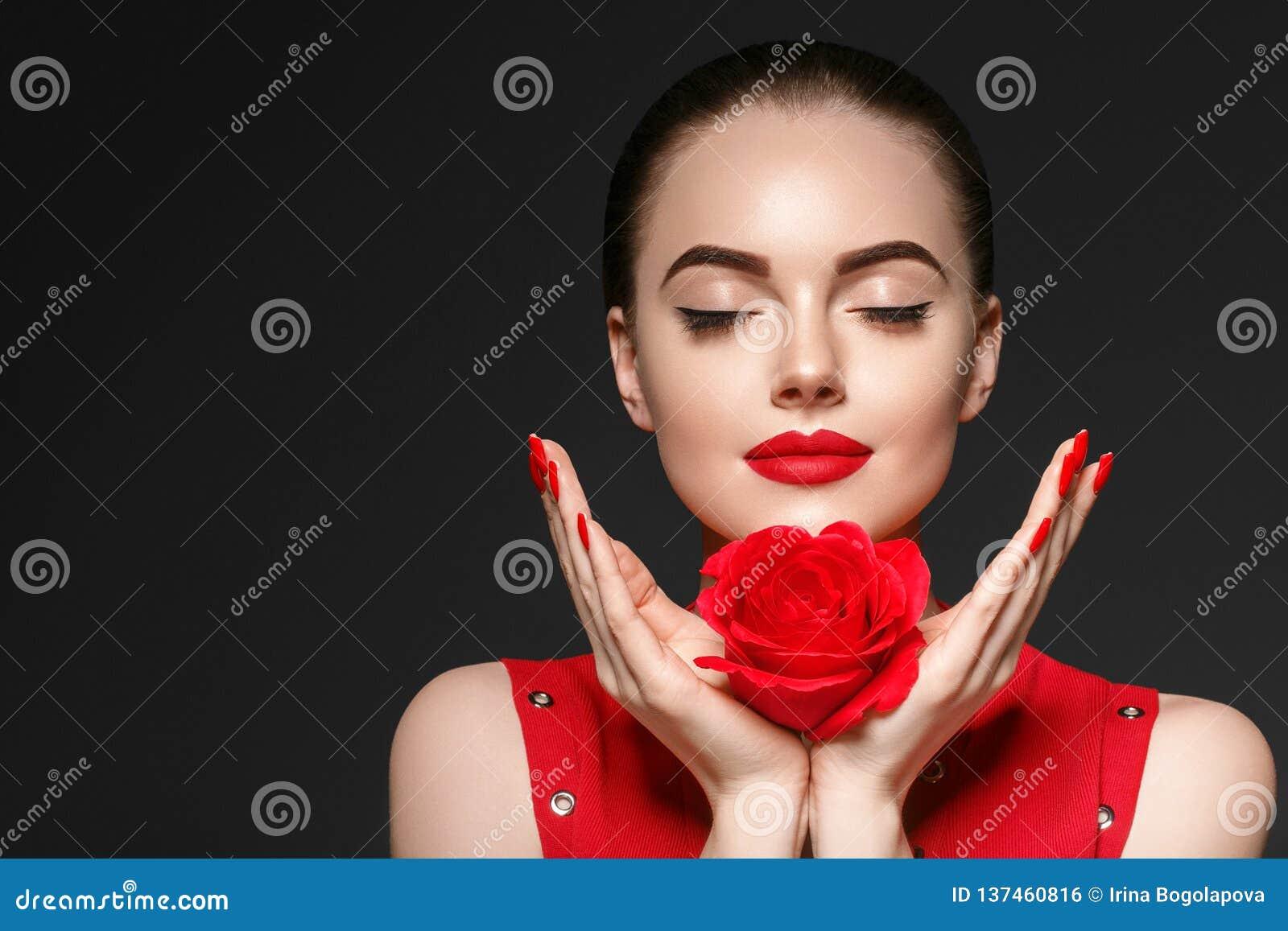 Mujer de la belleza con el pelo rizado hermoso y los labios de la flor color de rosa