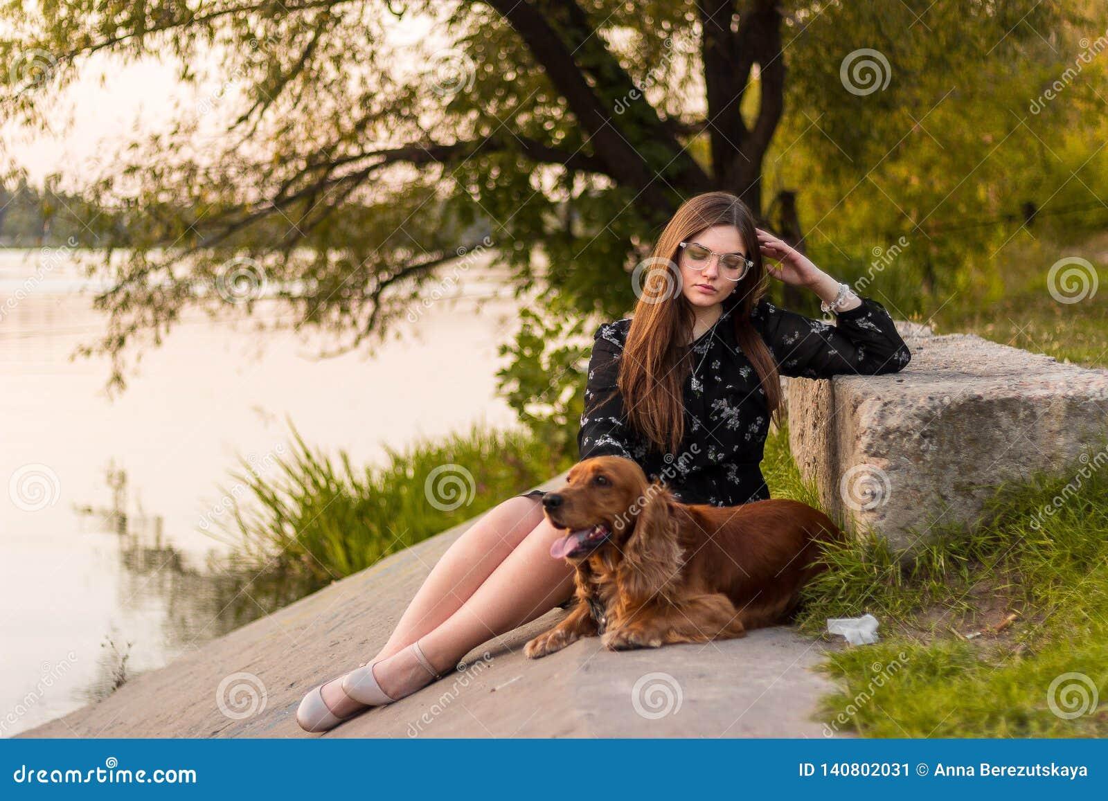 Mujer de la belleza con su perro que juega al aire libre