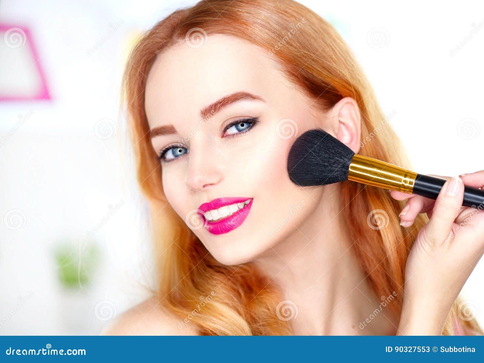 Mujer de la belleza que aplica maquillaje Muchacha hermosa que mira en el espejo y que aplica el cosmético