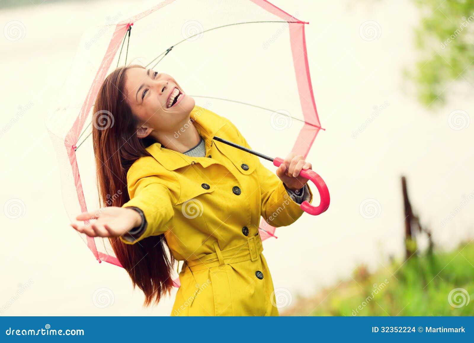 Mujer de la caída feliz después de paraguas que camina de la lluvia