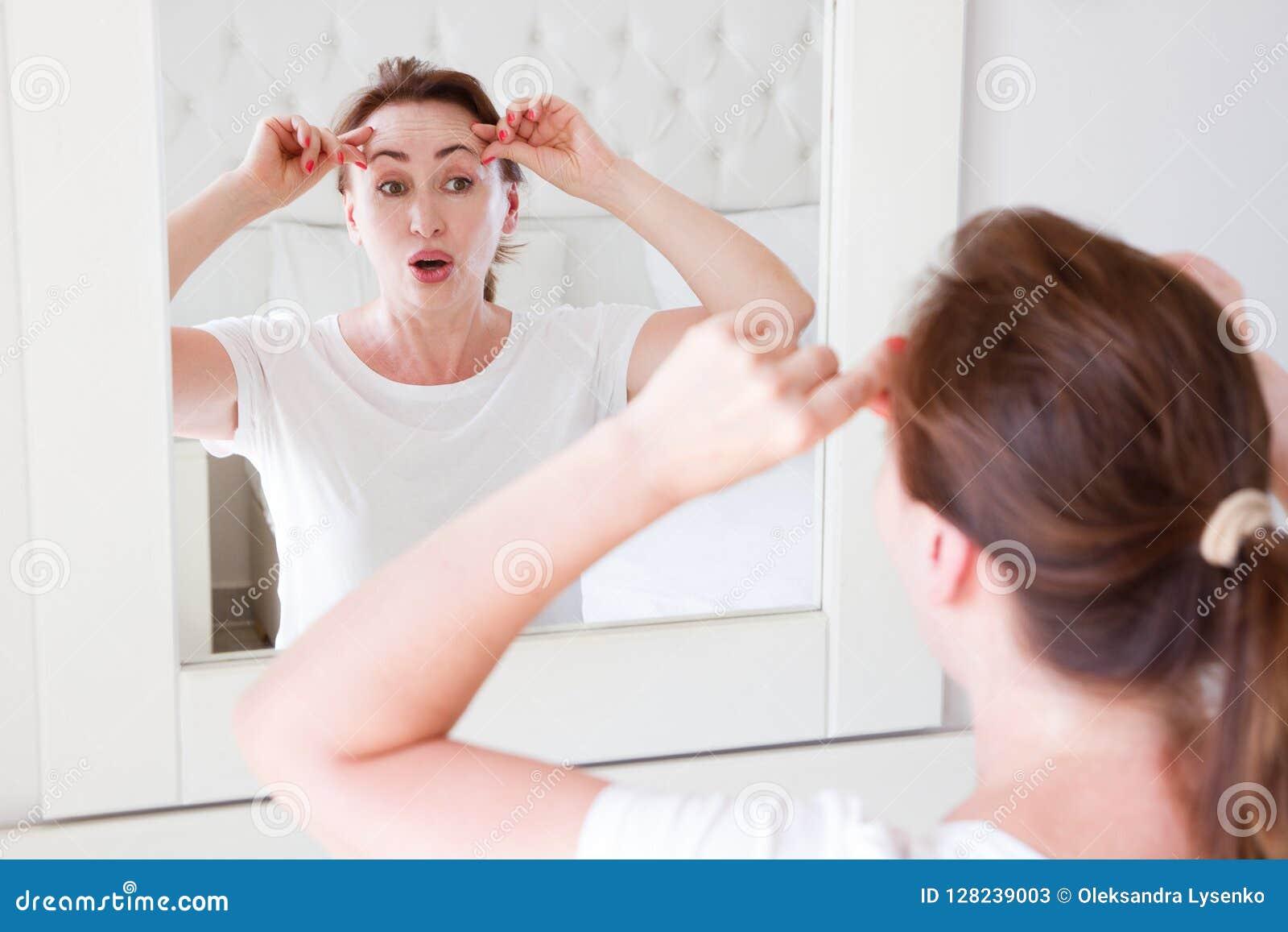 Mujer de la Edad Media que mira en espejo en la frente de la arruga de la cara en dormitorio Arrugas y concepto antienvejecedor d