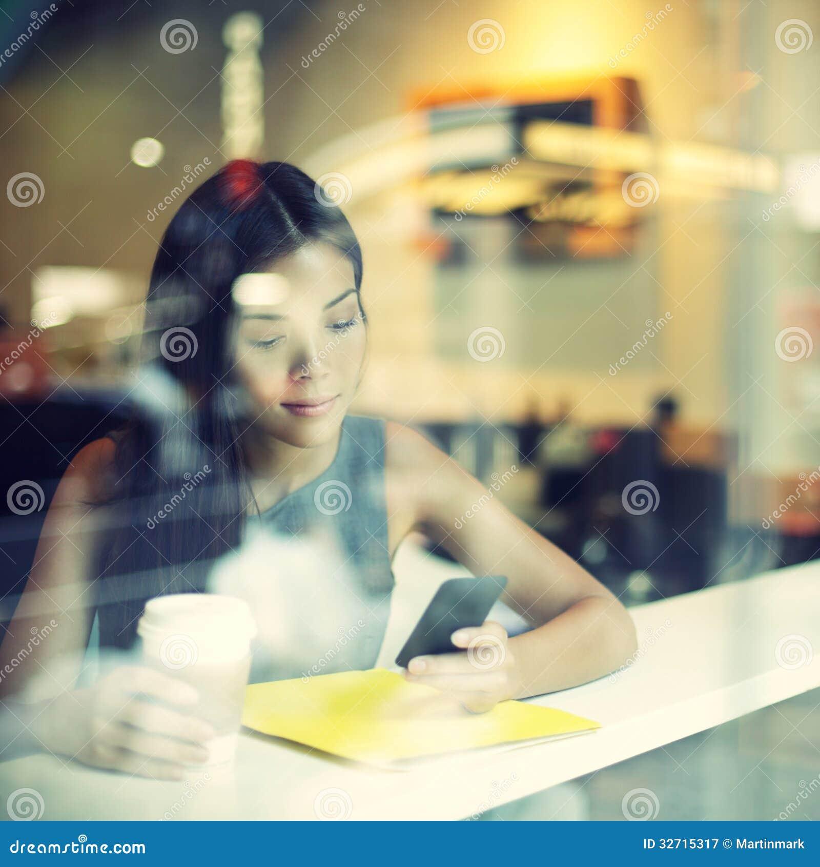 Mujer de la forma de vida de la ciudad del café en el café de consumición del teléfono