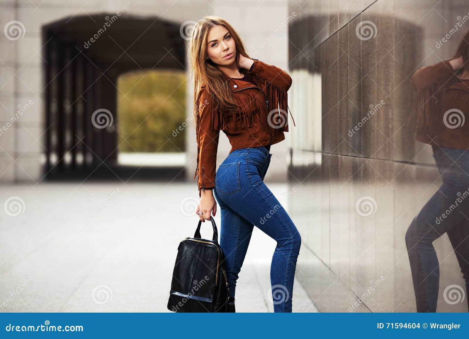 Mujer de la moda de los jóvenes en la chaqueta de cuero con el bolso